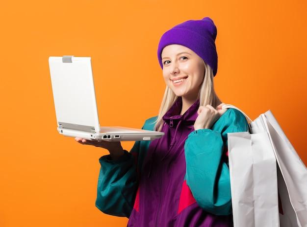 Stylowa kobieta w dresie z lat 90. z notatnikiem i pomarańczowymi torbami na zakupy