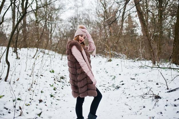 Stylowa kobieta w futrze i nakrycia głowy w zimowym lesie.