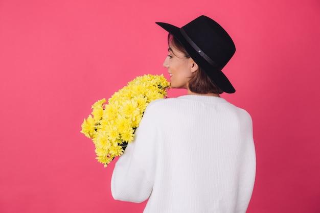 Stylowa kobieta w kapeluszu i dorywczo biały sweter na różowej czerwonej ścianie