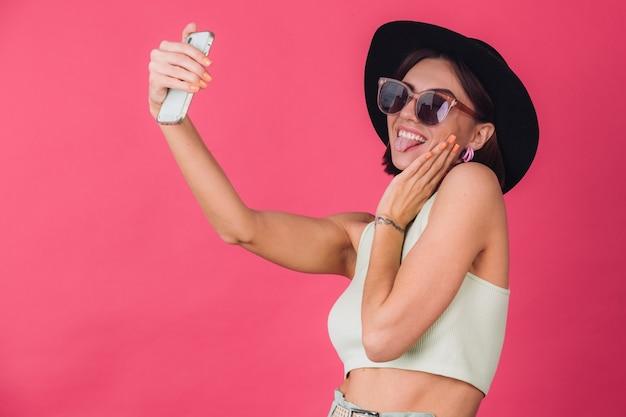 Stylowa kobieta w kapeluszu i okularach przeciwsłonecznych na różowej czerwonej ścianie