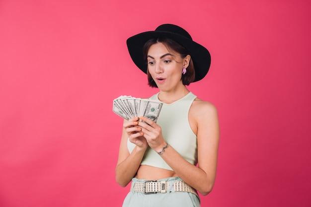 Stylowa kobieta w kapeluszu na różowej czerwonej ścianie