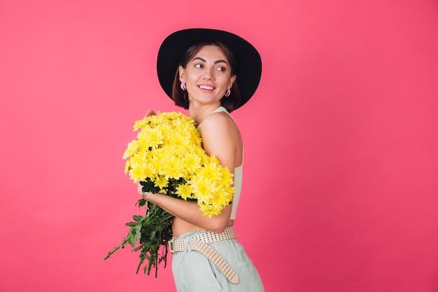 Stylowa kobieta w kapeluszu, ściskająca duży bukiet żółtych astry, wiosenny nastrój, spokojna uśmiechnięta izolowana przestrzeń