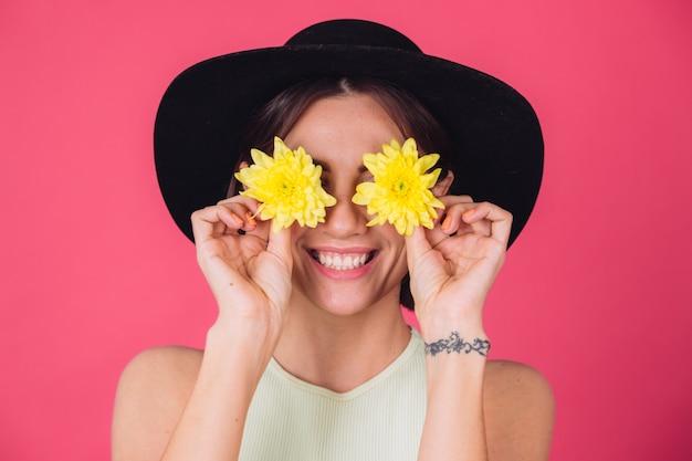 Stylowa kobieta w kapeluszu, uśmiech na twarzy, zakrywające oczy żółte astry, wiosenny nastrój, szczęśliwe emocje na białym tle