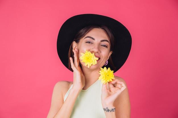 Stylowa kobieta w kapeluszu, uśmiechnięta z dwoma żółtymi astrami, uroczy trzymaj jeden kwiat w ustach wiosenny nastrój, szczęśliwe emocje odizolowana przestrzeń