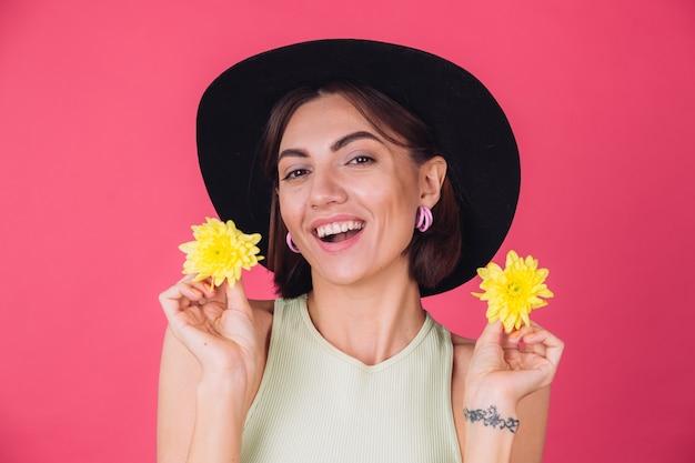 Stylowa kobieta w kapeluszu, uśmiechnięta z dwoma żółtymi astrami, wiosenny nastrój, szczęśliwe emocje na białym tle