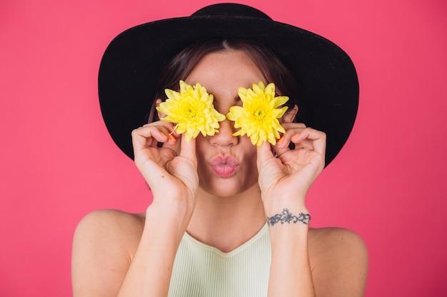 Stylowa kobieta w kapeluszu, wyślij pocałunek powietrza z żółtymi astrami, wiosenny nastrój, szczęśliwe emocje odizolowana przestrzeń