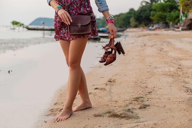 Stylowa kobieta w letniej sukience wakacje spacery na plaży z butami w ręku