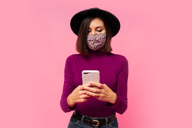 Stylowa kobieta w masce ochronnej i czarnym kapeluszu za pomocą telefonu komórkowego, stojąc.
