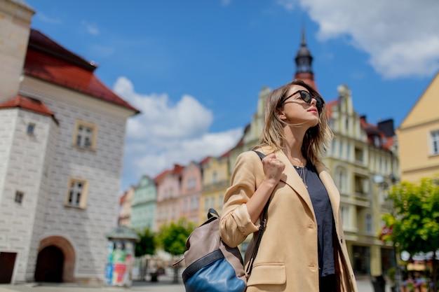 Stylowa kobieta w okularach przeciwsłonecznych i plecaku w wieku centrum miasta