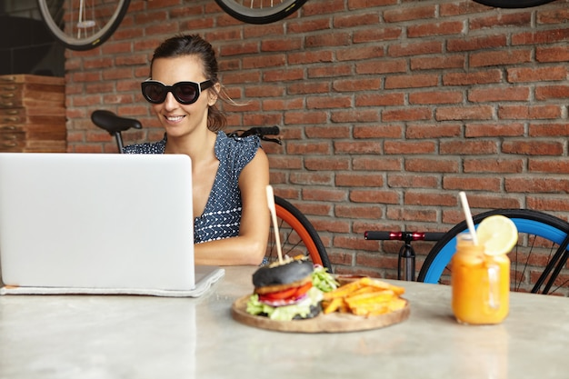 Stylowa kobieta w okularach przeciwsłonecznych, wysyłająca wiadomości przez sieci społecznościowe, przeglądająca internet na laptopie, korzystająca z komunikacji online