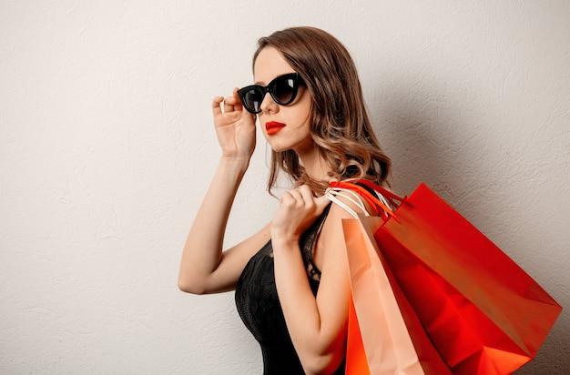Stylowa kobieta w okularach przeciwsłonecznych z torba na zakupy na biel ścianie