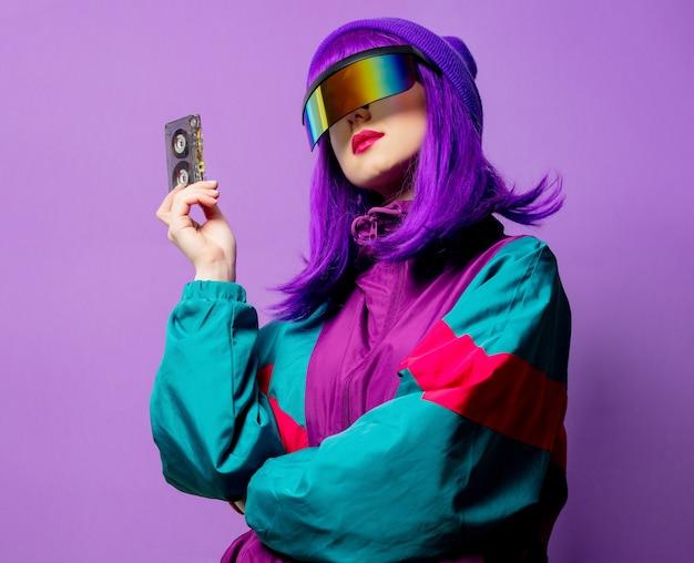 Stylowa kobieta w okularach vr i dresie z lat 80. z taśmą audio na fioletowej ścianie
