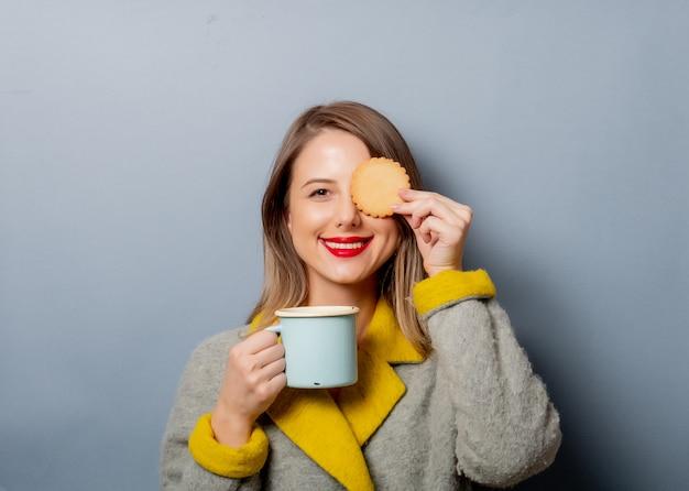Stylowa kobieta w płaszczu z filiżanką kawy i ciastkiem
