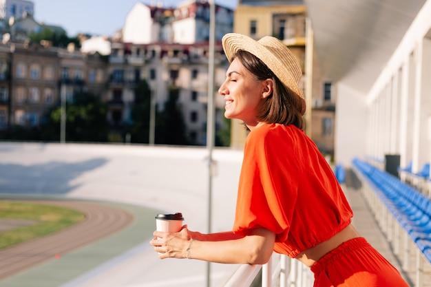 Stylowa kobieta w pomarańczowych ubraniach o zachodzie słońca na stadionie na torze rowerowym pozowanie z filiżanką kawy