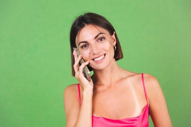 Stylowa kobieta w różowej jedwabnej sukience na zielono, zadowolona z telefonu komórkowego z ogromnym uśmiechem, prowadzi rozmowę telefoniczną call