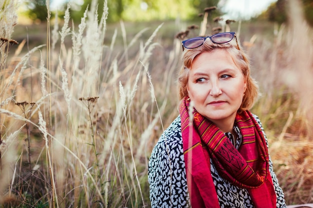 Stylowa kobieta w średnim wieku chłodzenie w jesiennym polu. starsza pani nosi ubrania i akcesoria jesienne. koncepcja harmonii i wewnętrznej równowagi