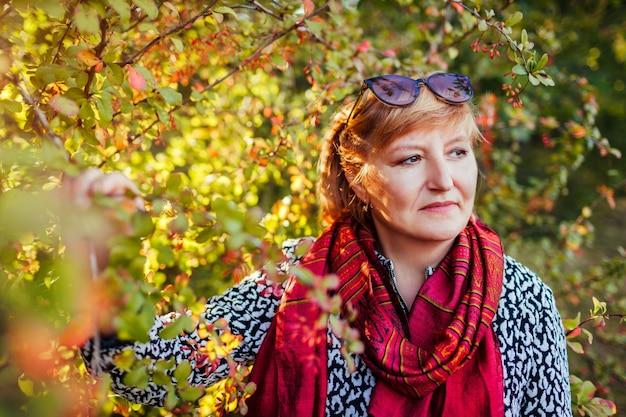 Stylowa kobieta w średnim wieku pozowanie w lesie jesienią. starsza pani nosi ubrania i akcesoria jesienne. moda strój