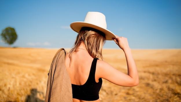 Stylowa kobieta w stylu kapelusz na polu pszenicy wsi