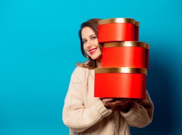 Stylowa kobieta w swetrze z pudełka na niebieską ścianą