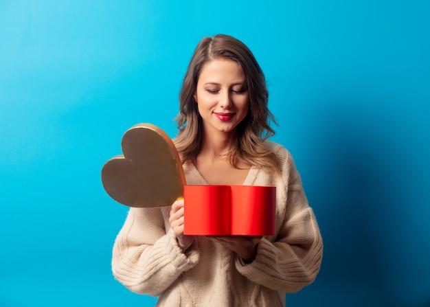 Stylowa kobieta w swetrze z szkatułce na niebieskiej ścianie