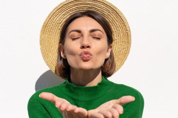 Stylowa kobieta w zielonym swobodnym swetrze i czapce na zewnątrz na białej ścianie spokojna i urocza wyślij pocałunek powietrza łapiącego promienie słoneczne
