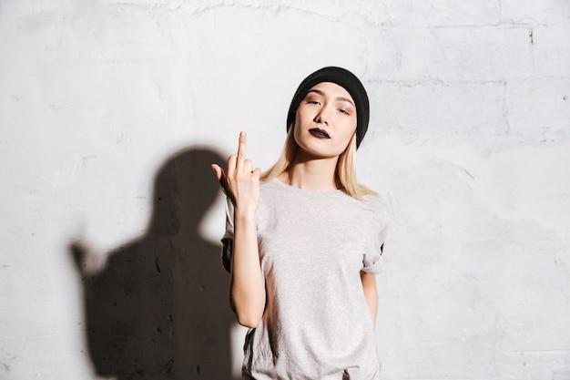 Stylowa kobieta z czarną pomadką stoi środkowego palec i pokazuje