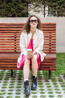 Stylowa kobieta z filiżanką kawy siedzi na ławce i patrzy w kamerę