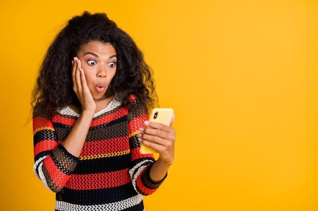 Stylowa kobieta z fryzurą afro pozuje na pomarańczowej ścianie