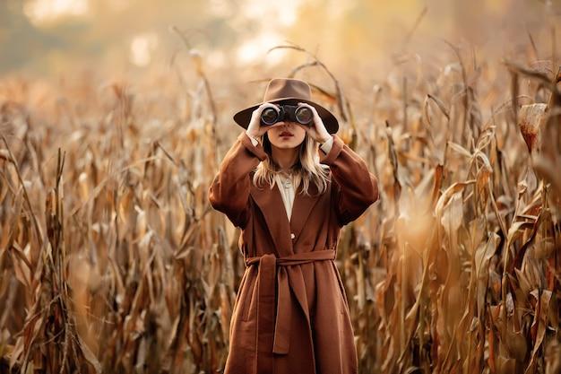 Stylowa kobieta z lornetką na polu kukurydzy w sezonie jesiennym