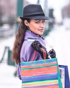 Stylowa kobieta z torbami na zakupy pokazująca kartę kredytową
