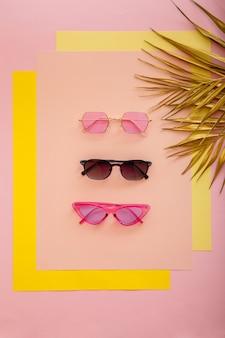 Stylowa kolekcja okularów przeciwsłonecznych w kolorze różowym w żółtej oprawie. letnie kobiece funky okulary na różowym tle ze złotymi liśćmi palmowymi. widok z góry.