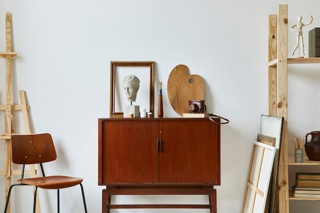 Stylowa kompozycja artystycznej przestrzeni roboczej z designerską komodą z drewna tekowego w stylu retro, krzesłem, regałem, ramami, sztalugą, dekoracją i eleganckimi akcesoriami osobistymi..