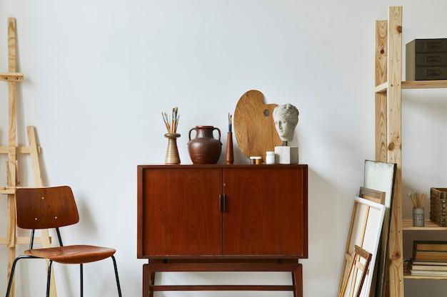 Stylowa kompozycja artystycznej przestrzeni roboczej z designerską komodą z drewna tekowego w stylu retro, krzesłem, regałem, ramkami na plakaty, sztalugą, dekoracją i eleganckimi akcesoriami osobistymi. szablon.