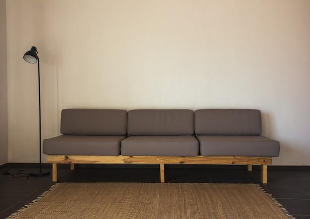 Stylowa kompozycja boho we wnętrzu salonu z designerską szarą sofą, drewnianym stolikiem kawowym, komodą i eleganckimi akcesoriami osobistymi. miodowo-żółta poduszka i kratka. przytulne mieszkanie. wystrój domu