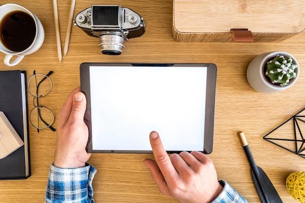 Stylowa kompozycja domowego biura z makiety ekranu tabletu, materiałów biurowych, filiżanki kawy, telefonu, aparatu fotograficznego, roślin i akcesoriów osobistych w koncepcji biznesowej.
