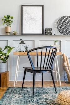 Stylowa kompozycja domowego biura z sofą, drewnianym biurkiem, designerskim krzesłem, makietą plakatową, dywanem, roślinami, książkami, lampą, artykułami biurowymi i akcesoriami osobistymi w nowoczesnym wystroju domu.