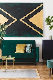 Stylowa kompozycja kreatywnego, nowoczesnego przestronnego wnętrza apartamentu z zieloną sofą, stolikiem kawowym i dodatkami w czarno-zielonej i złotej kolorystyce