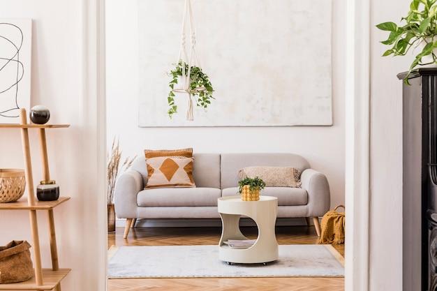 Stylowa kompozycja kreatywnego, przestronnego wnętrza mieszkania z szarą sofą, stolikiem kawowym, roślinami, dywanem i pięknymi dodatkami. białe ściany i parkiet.