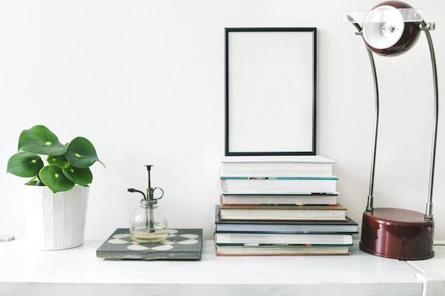 Stylowa kompozycja kreatywnego wnętrza salonu z czarną makietową ramą plakatową, roślinami w hipsterskich donicach, książkami, lampą i akcesoriami na białej półce. minimalistyczna koncepcja.