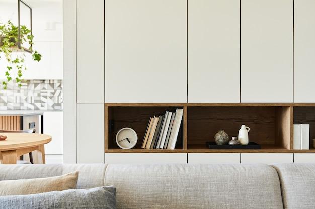 Stylowa kompozycja kreatywnych detali wnętrza salonu, takich jak książki, zegary i inne osobiste akcesoria. białe panele. kuchnia w tle. detale. szablon.