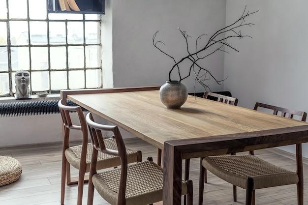 Stylowa kompozycja nowoczesnego wystroju jadalni z drewnianym stołem i krzesłami oraz akcesoriami. przestronny pokój z kreatywnymi ścianami i parkietem.