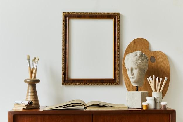 Stylowa kompozycja pracowni artysty z designerską komodą z drewna tekowego w stylu retro, ramą, książką, dekoracjami i akcesoriami do malowania.