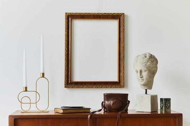 Stylowa kompozycja pracowni artystycznej z designerską komodą z drewna tekowego w stylu retro, makietową ramą plakatową, książką, dekoracją i eleganckimi dodatkami. szablon.