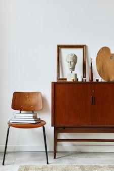 Stylowa kompozycja przestrzeni roboczej artysty z designerską komodą z drewna tekowego retro, ramkami, sztalugą, książką, dekoracjami i akcesoriami malarskimi.