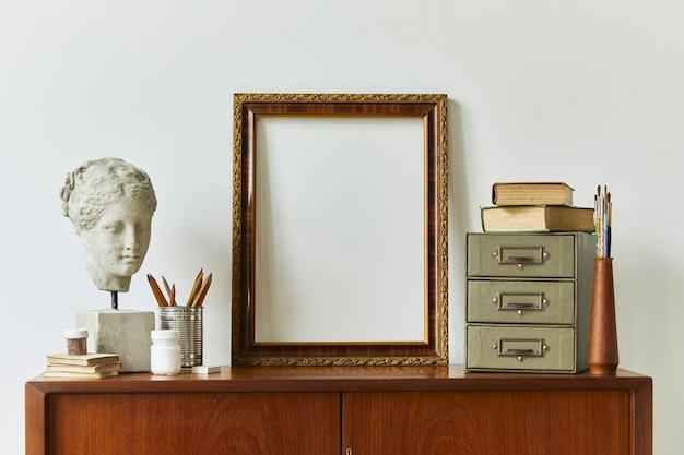 Stylowa kompozycja przestrzeni roboczej artysty z designerską komodą z drewna tekowego w stylu retro, ramą, książką, akcesoriami dekoracyjnymi i malarskimi.