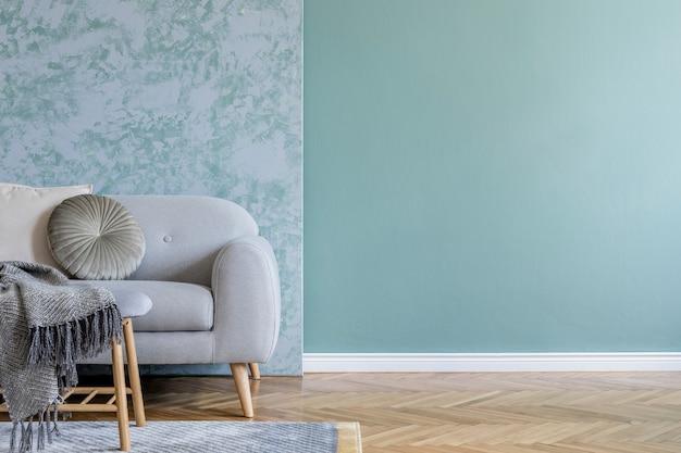 Stylowa kompozycja przytulnego salonu z sofą, drewnianą kostką, ładnymi detalami wnętrza i neutralnymi, eleganckimi poduszkami. zielono-szara kreatywna ściana i parkiet. styl skandynawski.