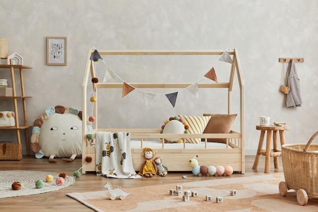 Stylowa kompozycja przytulnego skandynawskiego pokoju dziecięcego z drewnianym łóżkiem i stolikiem kawowym, pluszowymi i drewnianymi zabawkami oraz tekstylnymi wiszącymi dekoracjami. ściana kreatywna, na podłodze dywan. szablon.