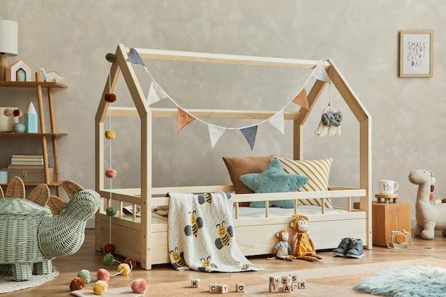 Stylowa kompozycja przytulnego skandynawskiego pokoju dziecięcego z drewnianym łóżkiem, półką, pluszowymi i drewnianymi zabawkami oraz tekstylnymi wiszącymi dekoracjami. neutralna kreatywna ściana, na podłodze dywan. szablon.