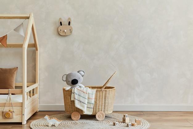Stylowa kompozycja przytulnego skandynawskiego wnętrza dziecięcego pokoju z łóżkiem, rattanowym koszem, pluszowymi i drewnianymi zabawkami oraz tekstylnymi wiszącymi dekoracjami. ściana kreatywna, na podłodze dywan. skopiuj miejsce. szablon.