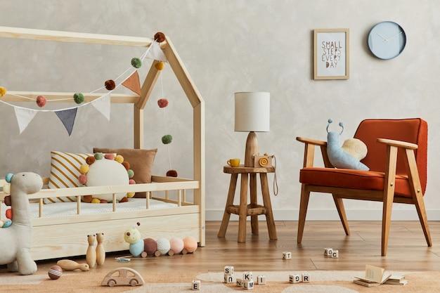 Stylowa kompozycja przytulnego skandynawskiego wnętrza pokoju dziecięcego z drewnianym łóżkiem, czerwonym fotelem, pluszowymi i drewnianymi zabawkami oraz tekstylnymi wiszącymi dekoracjami. ściana kreatywna, na podłodze dywan. szablon.